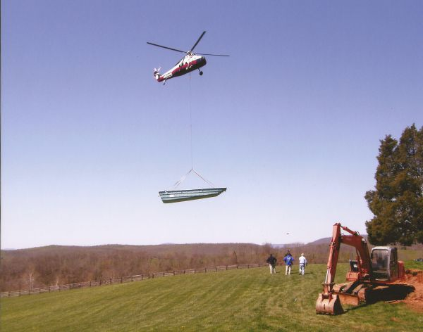 helicopter delivering a fiberglass pool