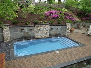 inground fiberglass pool with retaining wall and water features