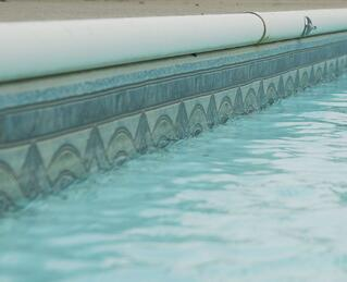 White aluminum C-channel coping on a vinyl liner pool