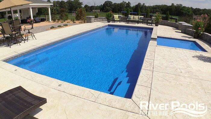 Greco fiberglass pool with separate tanning ledge, on textured concrete patio