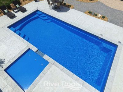 Greco fiberglass pool with tanning ledge built into the patio