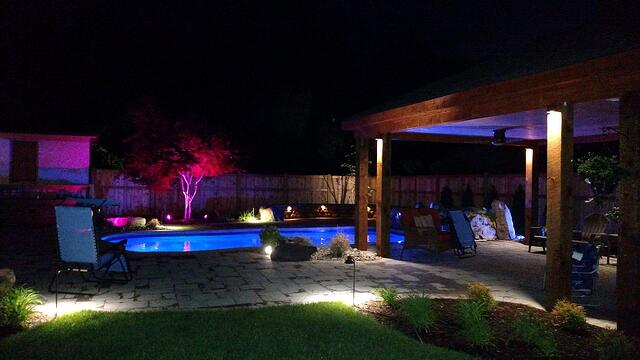 Pool and patio with multicolored lights, at night