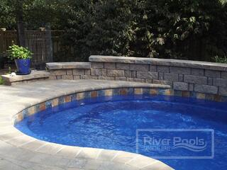 Earthy stone tile along the waterline of our fiberglass pool