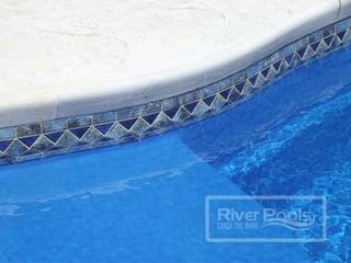 Blue stone mosaic tile along waterline of our fiberglass pool