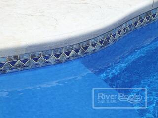 Blue stone mosaic tile along waterline of our fiberglass pool