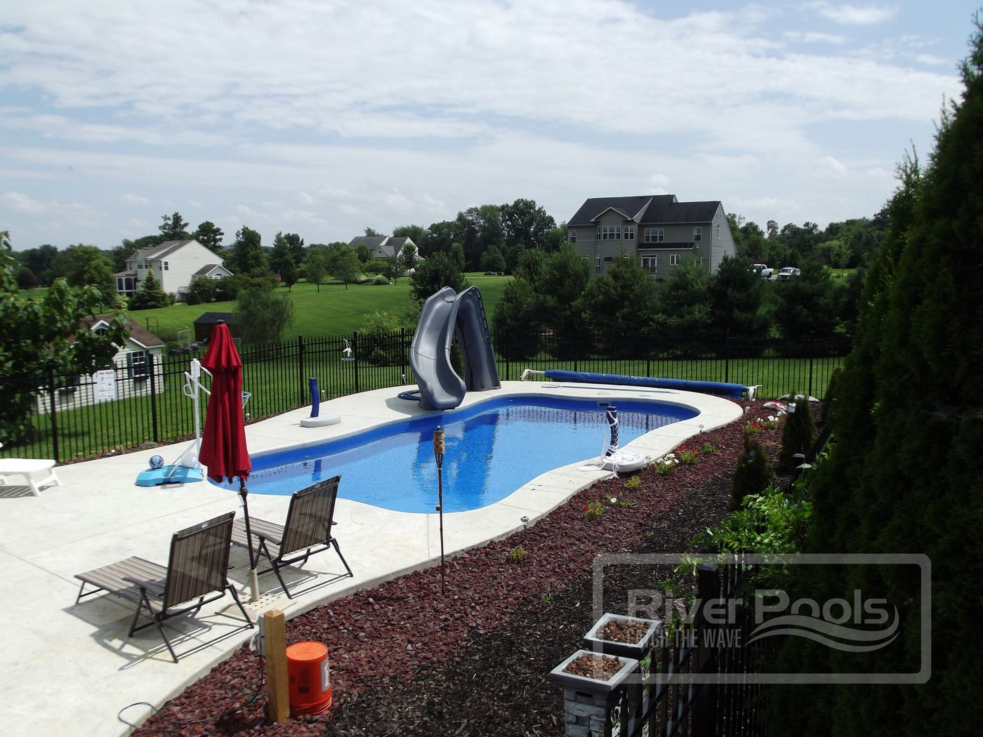 freeform fiberglass pool with deck chairs and slide