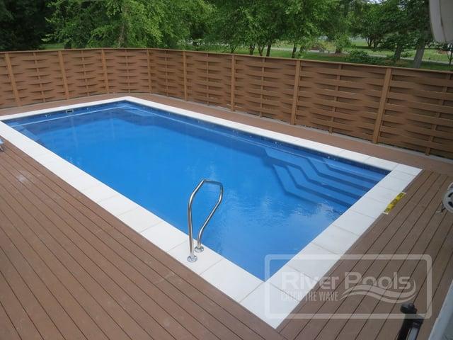 Inground fiberglass pool with wooden deck