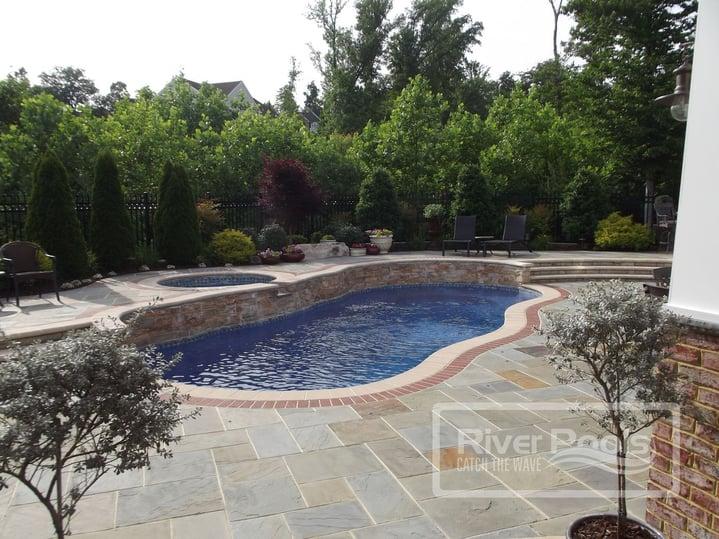 freeform fiberglass pool with elevated spa