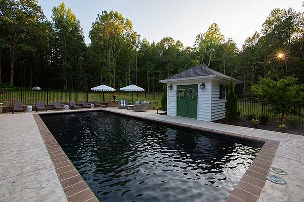 black bottom swimming pool with pool house