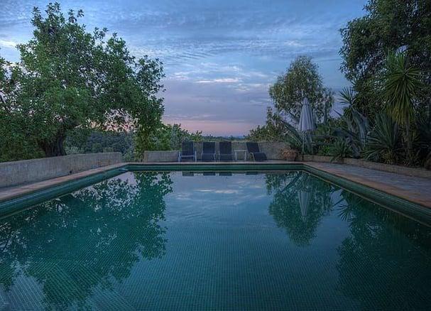 emerald green tiled dark bottom pool