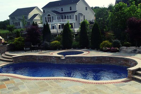 swimming pool with spa and elevated patio