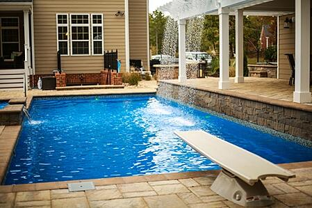 T40 pool in Maya Blue with diving board, waterfall off pergola, elevated tanning ledge, and contrasting tan/brown patio and coping