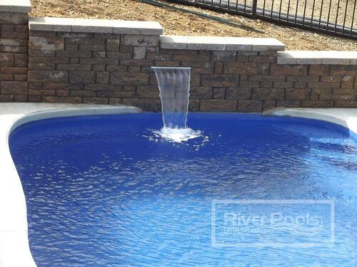 retaining wall with water cascade into freeform fiberglass pool