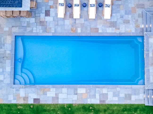 Fiberglass inground pool with stone patio