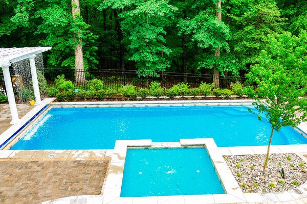 G36 fiberglass pool with elevated tanning ledge and green landscaping