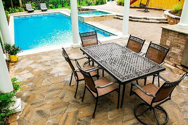 G36 fiberglass pool with elevated tanning ledge, pergola, stone patio, and table with chairs
