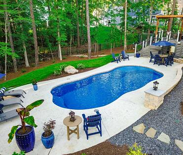 C Series pool with concrete patio and blue chairs