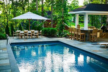 T40 pool model with stone patio, outdoor kitchen, and dining area