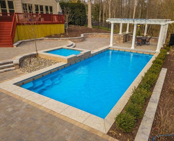 Greco (G36) fiberglass pool with elevated tanning ledge and pergola