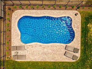 O Series pool with beige paver patio and coping
