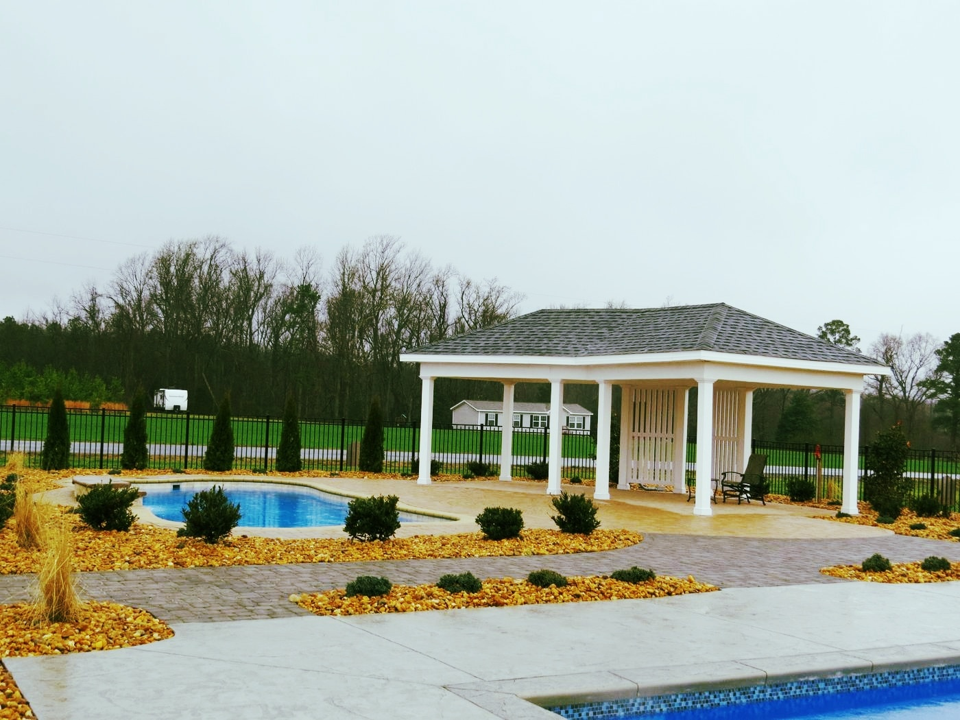 fiberglass pool with a permanent pavilion on the patio