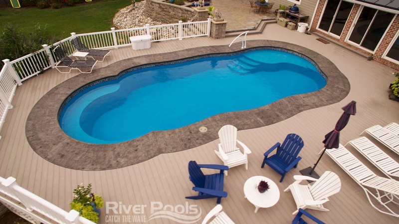 Crescent Cove fiberglass pool with deck chairs