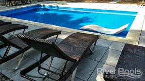 blue D Series pool with white lounge chair on tanning ledge