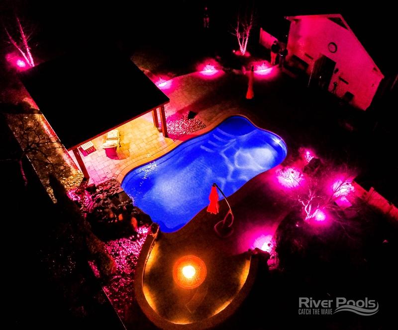 Oasis fiberglass pool with pink patio lights after dark