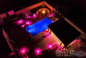 O Series pool (at night) with blue in-pool lights, pink patio lights, fire bowl, and kitchen on patio