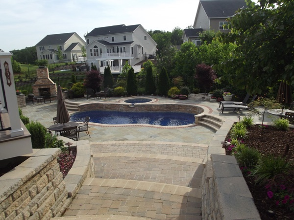 Evergreen trees and ferns around freeform fiberglass pool