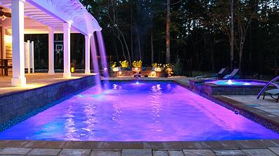 waterfall off pergola, bubblers in elevated tanning ledge, and colored lights in pool and patio