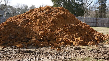 a big pile of dirt/clay, excavated for a fiberglass pool installation